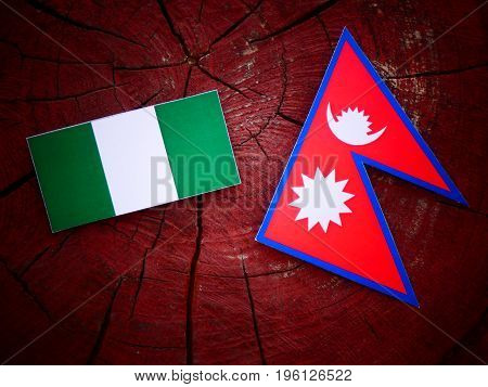 Nigerian Flag With Nepali Flag On A Tree Stump Isolated