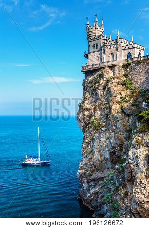 GASPRA CRIMEA - July 07 2011: The famous castle 'Swallow's Nest' or 'Lastochkino Gnezdo' on a rock and a passing yacht on a clear sunny day. Sight of the southern Crimean coast. The suburb of Yalta.