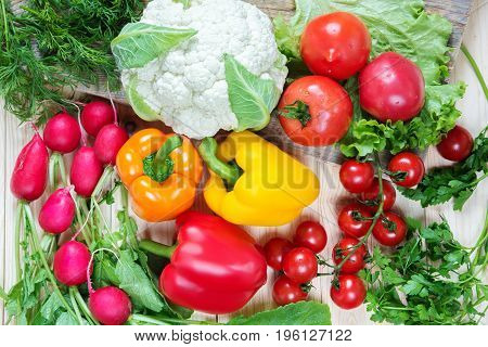 Different vegetables as a tomatoes cauliflower peppers radishes cherry tomatoes on a wooden background