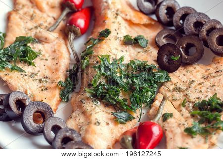 Cooked fillet of salmon with olives herbs and spicy red pepper on a white plate