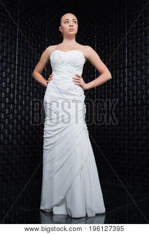 Thoughtful young woman wearing white wedding dress