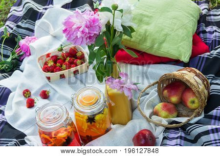 Picnic in the outdoor with strawberry apples and different cold beverages