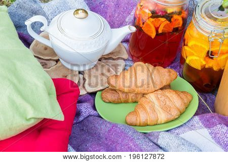 Picnic in the outdoor with tea croissants and different beverages