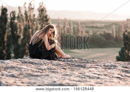 Blonde teen girl 14-16 year old sitting alone on rock over beautiful nature background. Looking at camera. Loneliness.