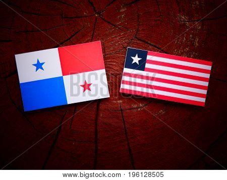 Panamanian Flag With Liberian Flag On A Tree Stump Isolated