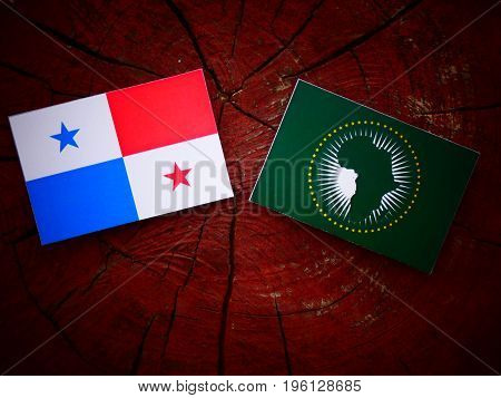 Panamanian Flag With African Union Flag On A Tree Stump Isolated