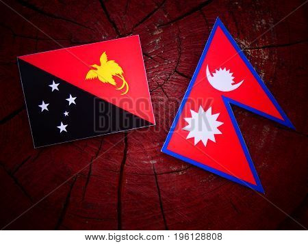Papua New Guinea Flag With Nepali Flag On A Tree Stump Isolated