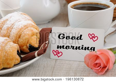 Breakfast of croissants chocolate filling cup of fresh morning coffee and a card with a wish Good morning.