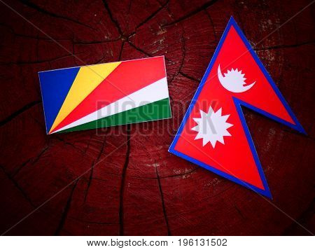 Seychelles Flag With Nepali Flag On A Tree Stump Isolated