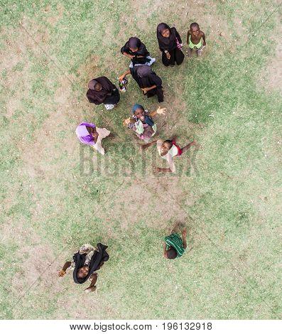 Zanzibar, Tanzania - July 15, 2016: Children of zanzibar, muslim girls wearing burka spinning and playing together, happy, topview