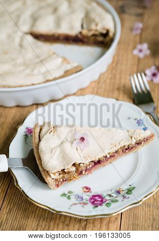 Close up of almond pie topped with meringue arranged on a flowery plate and old wooden table