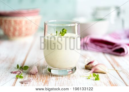 Close up of a homemade garlic sauce in a glass with garlic gloves arranged on rustic wooden table