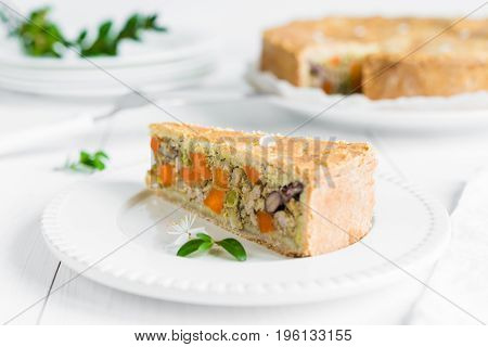Closeup of a piece of meat pie baked with vegetables carrots red beans and peas arranged on white plate and wooden table