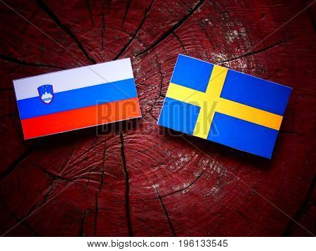 Slovenian Flag With Swedish Flag On A Tree Stump Isolated