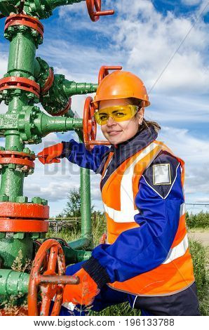 Woman worker in the oilfield repairing wellhead wearing orange helmet and work clothes. Industrial site background. Oil and gas concept.