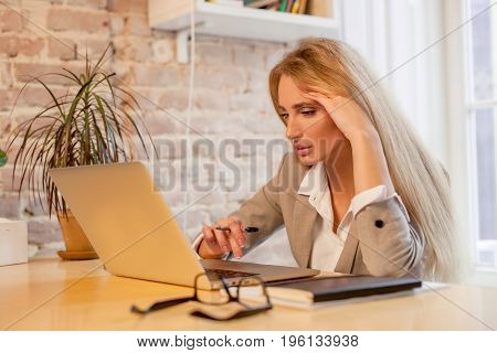 Long-haired blonde working with her laptop in a nice office. Woman wearing bussunes clothes.