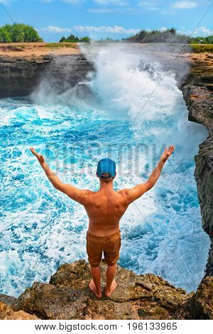Powerful sea surf crashing with splashes under stone cliffs. Surfer stand on high beach rock, look at breaking with water spray and foam waves. Healthy lifestyle, travel on summer family vacation.
