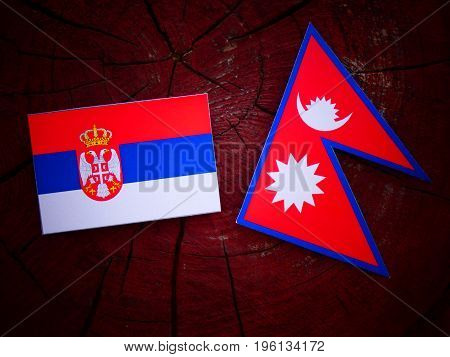 Serbian Flag With Nepali Flag On A Tree Stump Isolated
