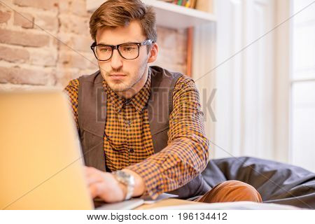 Young man wearing glasses sitting in front of a laptop and working.
