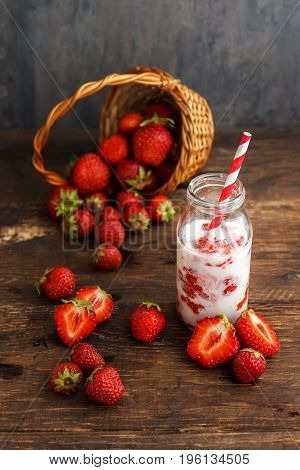 Milkshake or smoothie with strawberry in jar on black rustic background, fresh health food for breakfast and snack