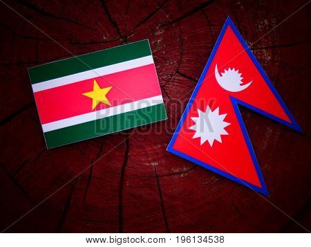 Suriname Flag With Nepali Flag On A Tree Stump Isolated