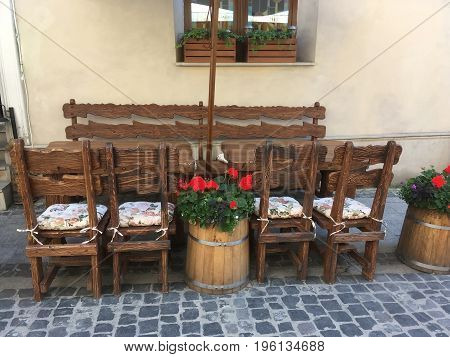 LVIV UKRAINE - JUNE 22: Creative oak tables and chairs without people in a street cafe in Lviv on June 22 2017 in Lvov Ukraine