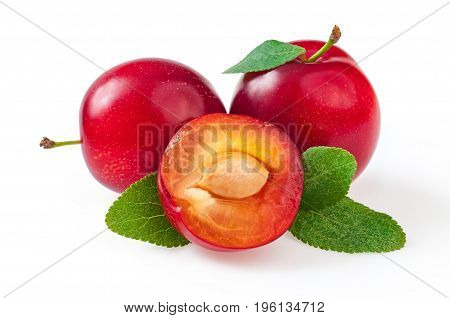 Sweet delicious red plums with leaves and half cut plum. Close-up isolated on white