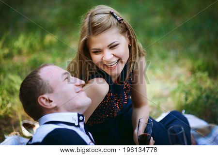 guy and girl having picnic in forest. Blond girl in dark blue dress and man in light trousers and shirt. couple looking in each other and smiling. happy family relationship concept
