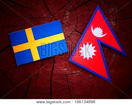 Swedish Flag With Nepali Flag On A Tree Stump Isolated