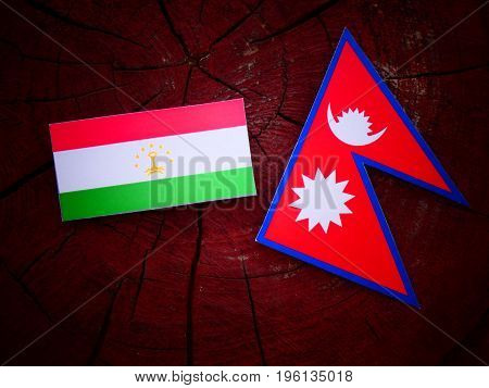 Tajikistan Flag With Nepali Flag On A Tree Stump Isolated