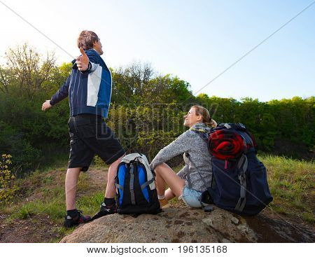 Couple of Hikers with backpacks resting guy take a deep breath with open arms. Travel vacation holidays and adventure concept. Forest Mountain landscape background