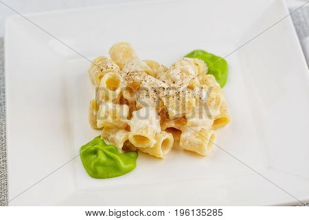 Penne pasta with a creamy sauce with parmesan cheese and spinach sause on a white plate on a marble surface