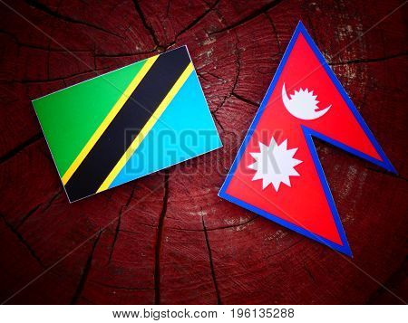Tanzanian Flag With Nepali Flag On A Tree Stump Isolated