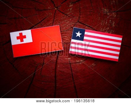 Tongan Flag With Liberian Flag On A Tree Stump Isolated