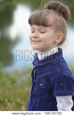 Portrait of adorable little girl with beautiful hairstyle taking a deep breath with closed eyes and smile on lake background.