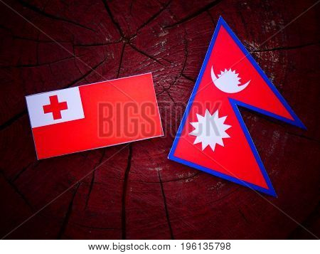 Tongan Flag With Nepali Flag On A Tree Stump Isolated