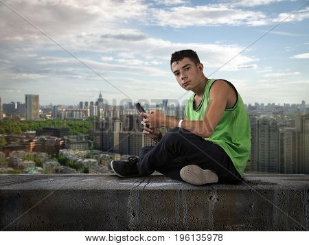 Young man with mobile phone on the roof. Teenager sits on top. Panorama of the city