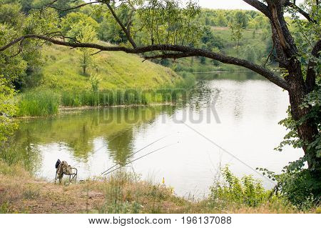 Beautiful summer day near the river with two lonely fishing rods