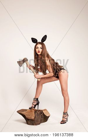 Attractive young woman posing on a white background wearing combination and rabbit-ears and holding an ax.