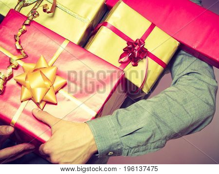 Holiday xmas winter time season and special occasion. Closeup of male hands holding a lot of presents gifts boxes