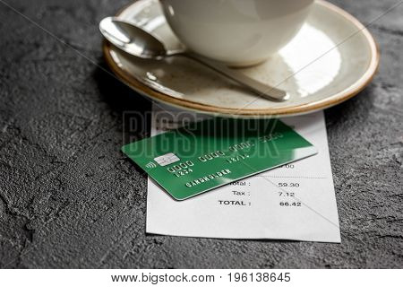 credit card for paying, cup of coffee and check on cafe gray stone desk background