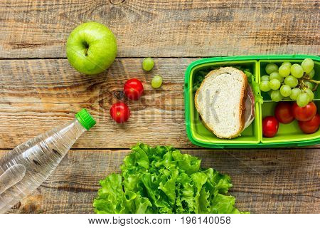 homemade lunch with apple, grapes and sandwich in green lunchbox on wooden table background top view