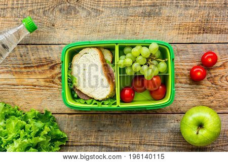 homemade lunch with apple, grape and sandwich in green lunchbox on wooden table background, top view