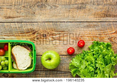 homemade lunch with apple, grape and sandwich in green lunchbox on wooden table background, top view mock-up