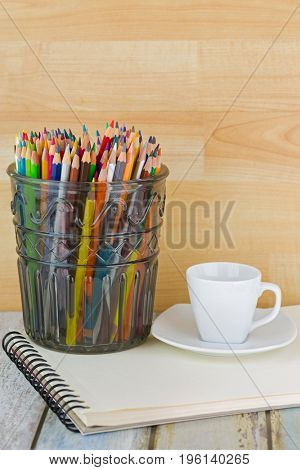 Hot Espresso coffee cup next to big glass full of coloring colored pencils on sketch drawing book.
