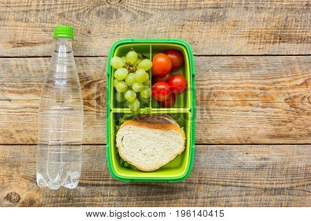 homemade lunch with bottle, grape and sandwich in green lunchbox on wooden table background, top view mock-up