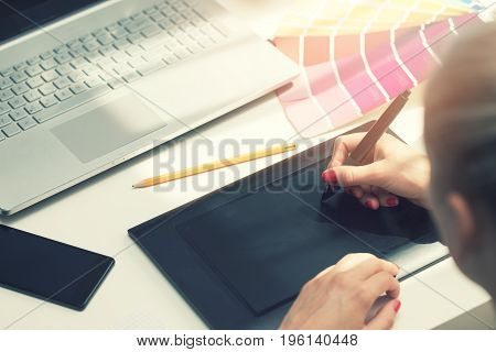 freelance graphic designer using digital drawing tablet