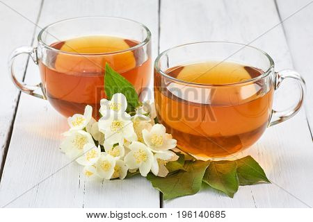 Two Cups Of Jasmine Tea And Jasmine Flowers On A White Wooden Table