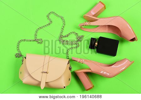 Sandals, Handbag And Perfume Bottle Isolated On Green Background