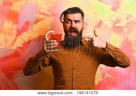 Bearded man long beard. Brutal caucasian surprised hipster with moustache in brown shirt holding tropical alcoholic fresh cocktail with orange piece on colorful texture background
